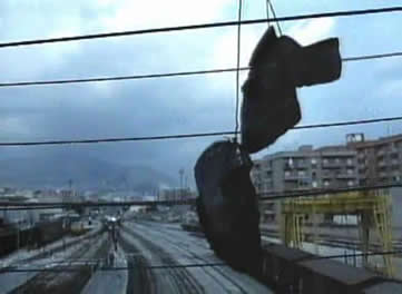 一趟列车缓缓地驶入了人们在片头所看到的在行人天桥上挂着一双鞋子的火车站.