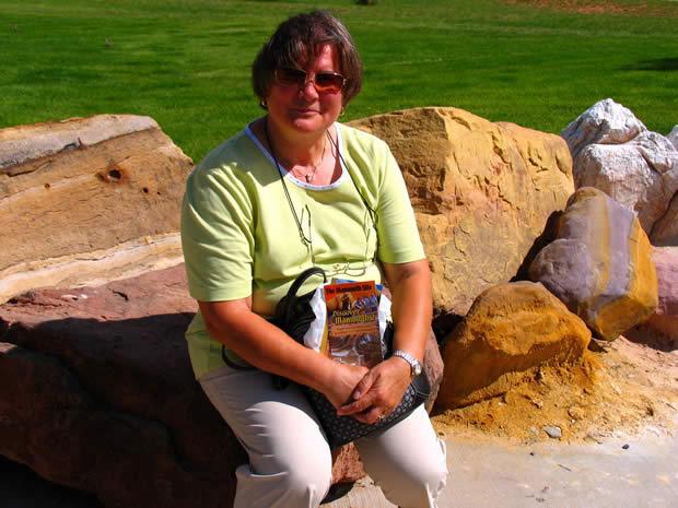 我的夫人玛莉亚, 坐在多彩的山顶岩石上.