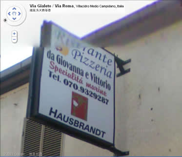 """牌子上的文字是:""""Ristorante Pizzeria da Giovanna e Vittorio Specialita marine Tel 070 932 9287 HAUSBRANDT"""" 译文是""""乔瓦尼和维托里奥比萨餐厅 海事专用电话 070.9329287 伯兰特住宅"""""""